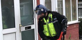 Officer using a hammer to open a door in Alum Rock
