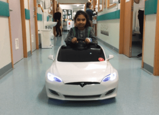 Child driving down hospital corridor in a Tesla donated by Tesla Owners Group UK